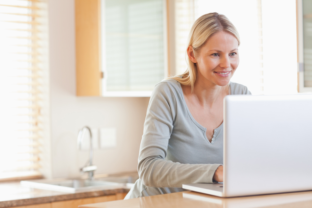 Smiling young woman typing on her laptop