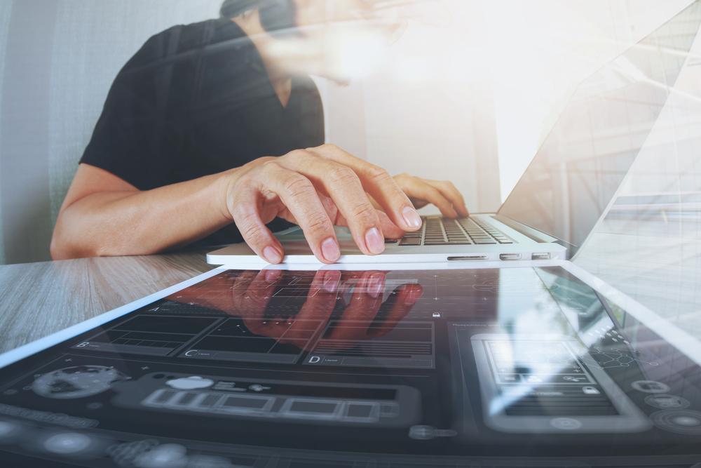 Website designer working digital tablet and computer laptop with smart phone and digital design diagram on wooden desk as concept