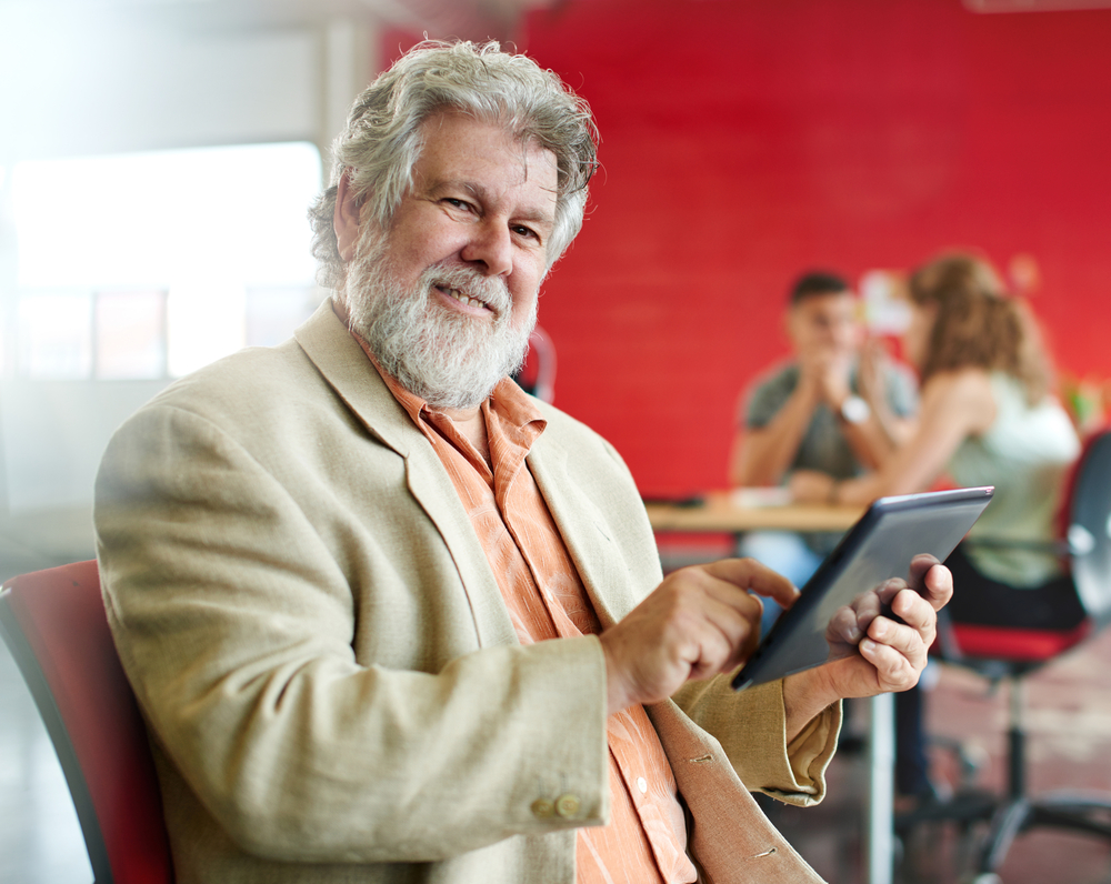 Confident male designer working on a digital tablet in red creative office space-9